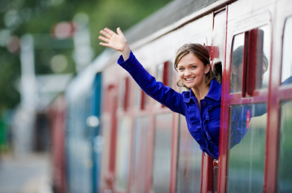 Young woman waving goodbye as she leans out of a railway carriage window